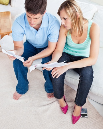 Young caucasian couple looking at bills sitting on the sofa Stock Photo - 10254395