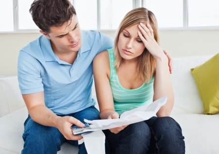 Worried woman looking at bills with her boyfriend holding a calculator sitting on the sofa photo