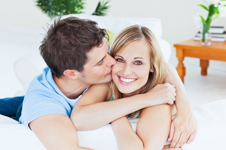 casal: Portrait of an attentive boyfriend kissing his smiling girlfriend relaxing in the living-room