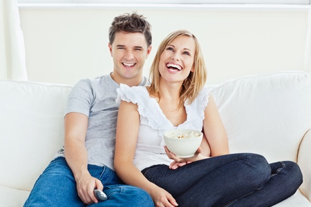 pareja en casa: Pareja feliz viendo una pel�cula con pop-corn sentado en el sof� en la sala de estar Foto de archivo