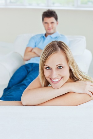 Portrait of a beautiful woman relaxing on the sofa with her boyfriend sitting behind photo
