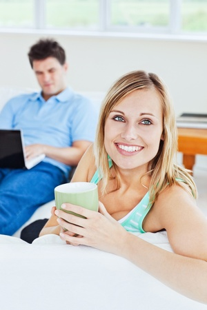 computer use: Attractive woman relaxing with a cup of coffee having her boyfriend using a laptop in the background