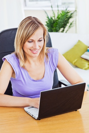 Beautiful woman writing on her laptop sitting at a table in the living-room Stock Photo - 10254469