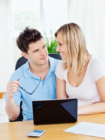 finance girl: Lovely couple sitting together at a table to work on a laptop with calculator Stock Photo