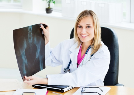 Beautiful female doctor showing an x-ray to the camera sitting in her office photo