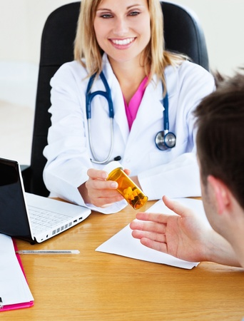 Portrait of an attractive doctor giving pills to her patient during an appointment photo