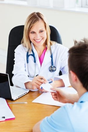 doctor's appointment: Beautiful doctor giving a prescription to her male patient sitting in her office