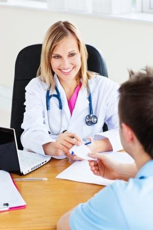 recetas medicas: Doctor hermosa dar una receta a su paciente var�n sentado en su Oficina Foto de archivo