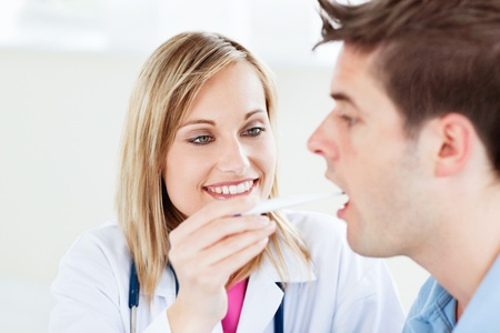 Portrait of a female doctor taking a saliva sample of a male patient with cotton-bud photo