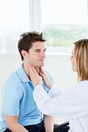 Vrouwelijke arts examinating de keel van een gelukkig patiënt zit in haar kantoor