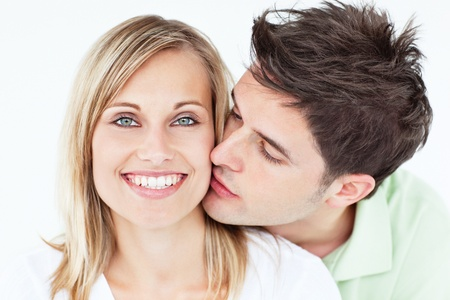 Portrait of a cute man kissing his girlfriend against a white background Stock Photo - 10254468