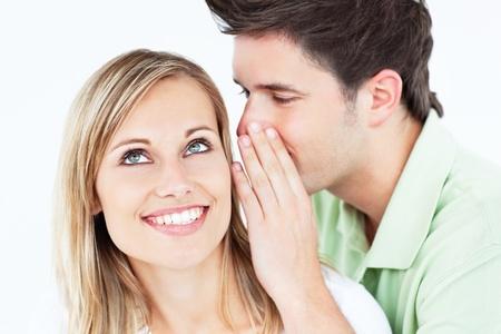 Jonge man fluisteren iets aan zijn attente vriendin