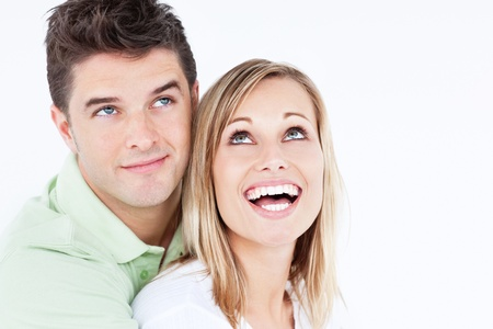 Portrait of a joyful couple looking at the top standing against a white background photo