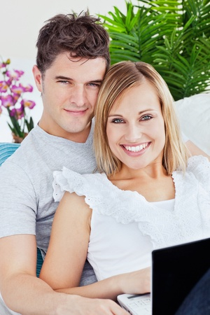 Portrait of a young caucasian couple with laptop relaxing on the sofa photo