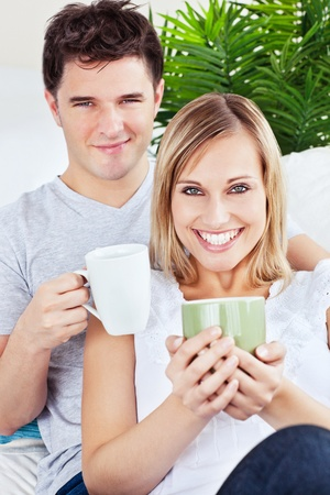 Lovely couple resting on the sofa holding cups of coffee Stock Photo - 10254493