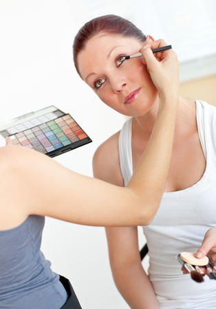 Close-up of a woman making-up her female friend at home photo