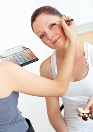 Happy young woman with make-up accessories being made-up by a friend photo