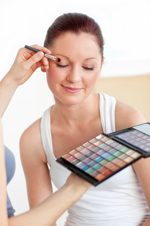 Attractive woman having a make-up lesson at home photo