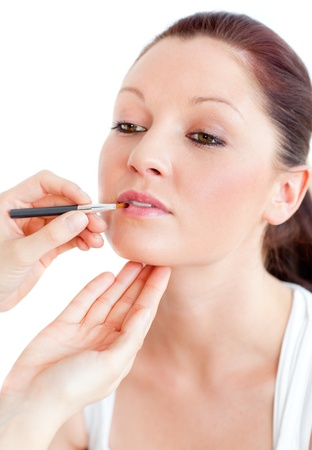 Close-up of a proud woman being make-up by a professional artist photo