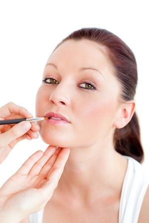 Portrait of a woman being make-up by a professional artist photo
