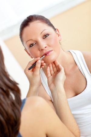 Make-up artist applying some lipstick on an attractive woman photo
