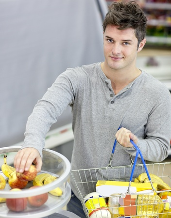 Healthy man with shopping-basket buying fruits in a grocery shop Stock Photo - 10254149
