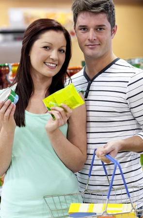 sho: Portrait of a young couple buying cans standing in a grocery sho
