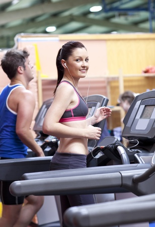 musculation: Athletic woman listening to the music while using a treadmill in a sport centre