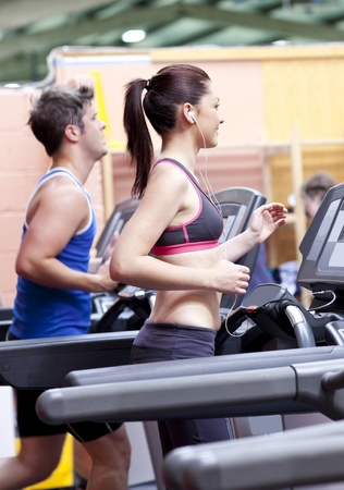 Pretty woman with earphones using a treadmill with her boyfriend in a fitness centre photo