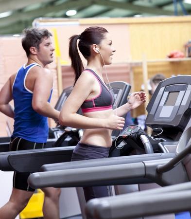 Couple en santé fonctionne sur un tapis roulant dans un centre sportif