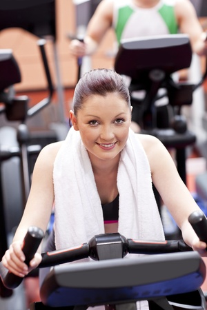 Athletic woman using a bicycle in a sport centre Stock Photo - 10254146