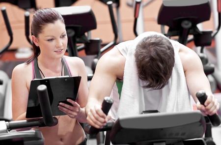 Hombre agotado haciendo ejercicios, mientras que su entrenador es mirar sus resultados