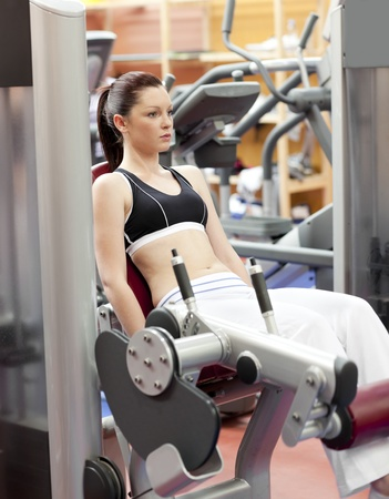 fitness equipment: Attractive woman lifting weights with a leg press in the room of a sport centre Stock Photo
