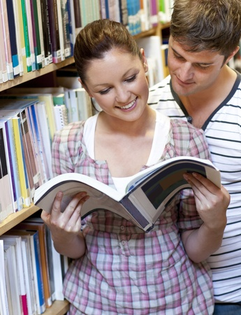 Two students enjoying reading a book together in the library Stock Photo - 10254312