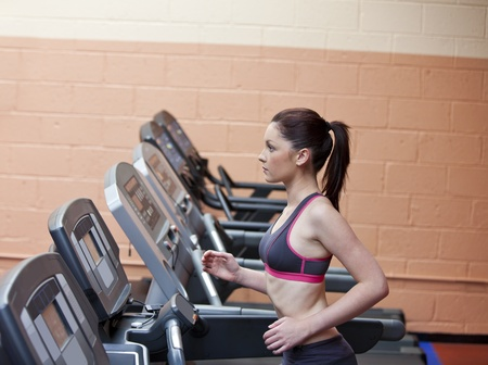 Serious female athlete doing exercises on a treadmill in a fitness centre photo