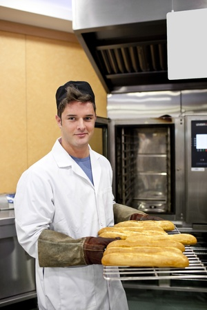 Happy baker showing his baguettes to the camera standing in his kitchen photo