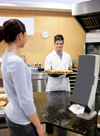 Portrait of a baker holding bread and baguette smiling at a customer in the queue Stock Photo - 10254086