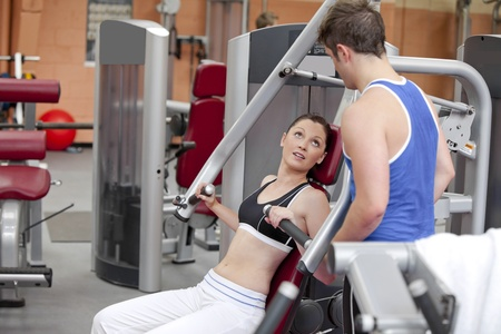 musculation: Sporty woman sitting on a shoulder press talking with her coach in a fitness centre Stock Photo