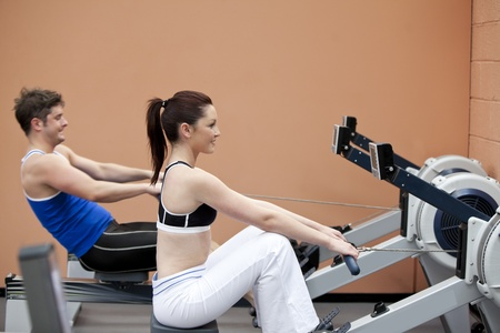 Young couple using a rower in a sport centre photo