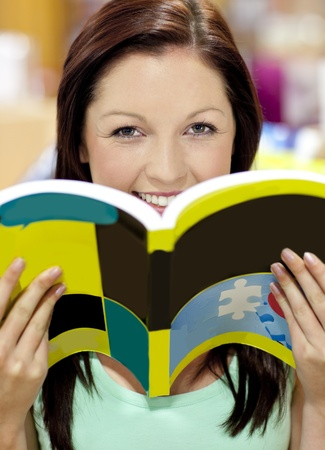 Portrait of a beautiful woman holding a book in a library smiling at the camera  photo