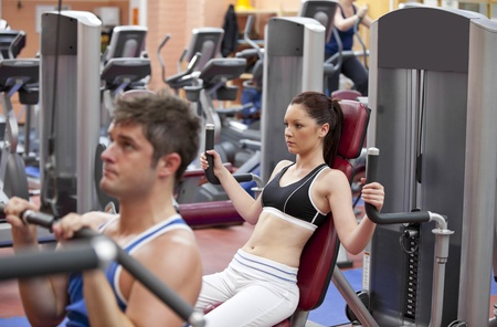 Concentrated couple using shoulder press in a fitness centre photo