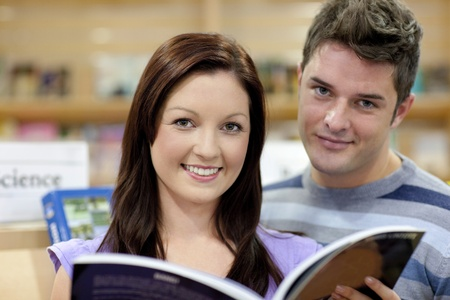 Portrait of a cute couple reading a book in a shop photo