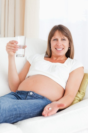 Pretty pregnant woman taking a pill while lying on a sofa in her apartment photo