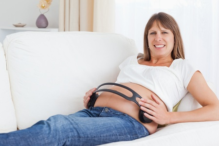 Smiling pregnant woman with headphones on her belly looking at the camera Stock Photo - 10780442