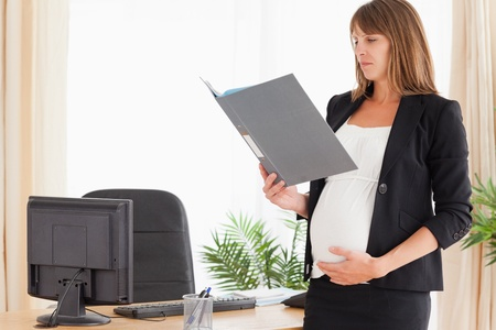 Beautiful pregnant female holding a file while standing in the office photo