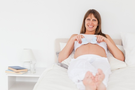 Charming pregnant female playing with little socks while lying on a bed in her apartment photo
