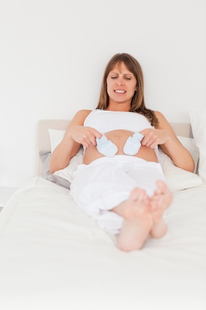 Good looking pregnant female playing with little socks while lying on a bed in her apartment photo