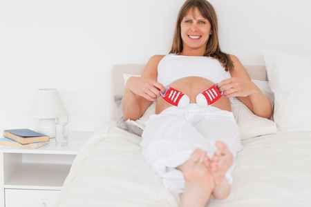 Beautiful pregnant female playing with little red shoes while lying on a bed in her apartment photo
