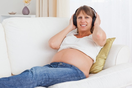 Pregnant woman listening to music while lying on a sofa Stock Photo - 10780391