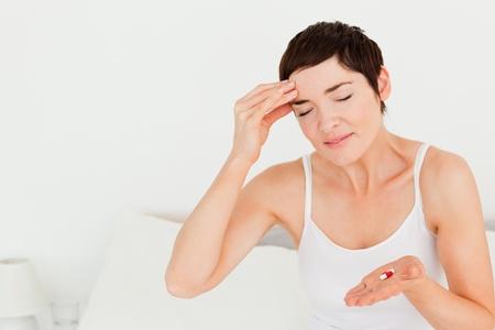 afflict: Cute brunette having a headache in her bedroom